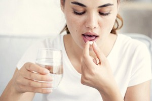 young woman taking pill with glass of water