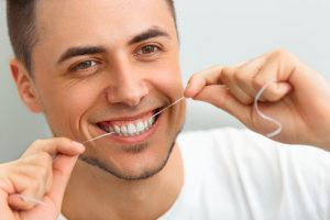 young man smiling while flossing