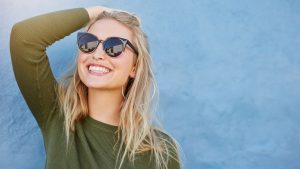 woman smiling and wearing sunglasses