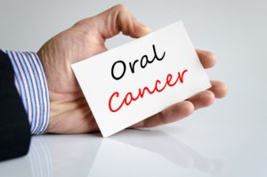 Dentist in Hulen holding oral cancer card